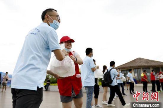 活动现场,志愿者正在传递鱼苗。 李思源 摄