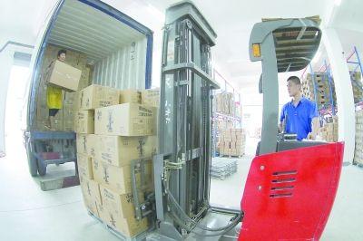龙海市联众物流内,员工在卸货。