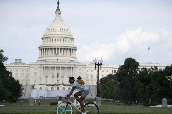 6月26日,一名男子骑车经过美国首都华盛顿的国会大厦。美国疾病控制和预防中心网站26日更新的数据显示,过去24小时全美新增确诊病例40588例,为2个多月以来单日新增病例数最高纪录。美国副总统彭斯表示,近期新增病例年轻人居多,约半数为35岁以下群体。(新华社记者 刘杰 摄)