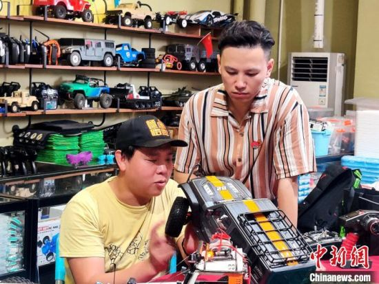 江凯与模友正在探讨遥控模型仿真车。 叶秋云 摄