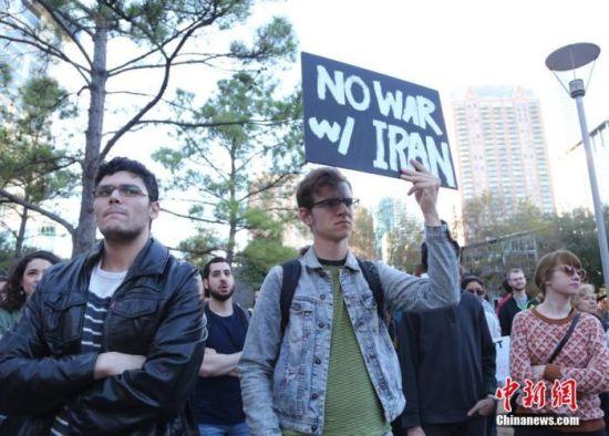 """当地时间1月5日,美国石油重镇休斯敦的民众举行反战集会,谴责美军炸死伊朗伊斯兰革命卫队下属""""圣城旅""""指挥官卡西姆·苏莱曼尼,反对美军向中东地区增派约3千名士兵的决定。图为集会民众手持""""不对伊朗发起战争""""的标语。 中新社记者 曾静宁 摄"""