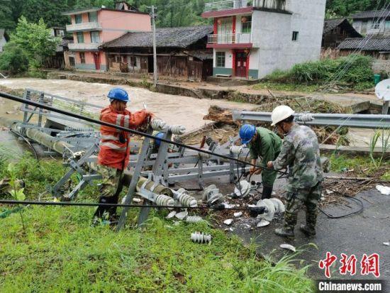 7月9日,福建南平光泽县供电公司的抢修人员在光泽县司前乡云际村抢修受损的10千伏云际线。 吴其微 摄