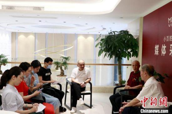 """高票荣膺""""社区英雄""""第一名的姚景良老人接受媒体记者采访。主办方供图"""