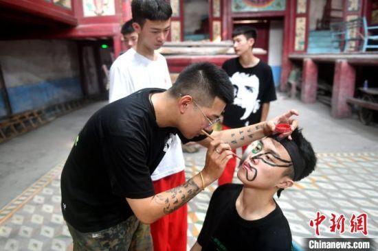 """福州锦麟轩八将团团长黄杜飞正在给""""00后""""团员画脸谱。 吕明 摄"""
