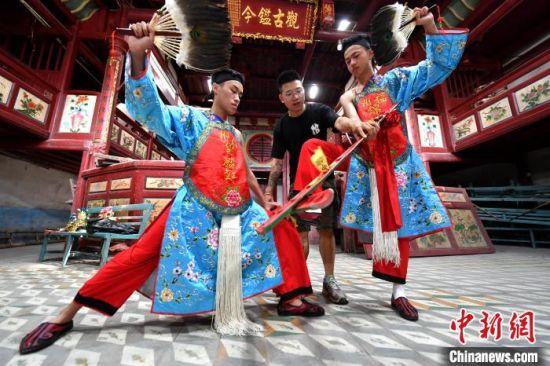 """福州锦麟轩八将团团长黄杜飞正在教""""00后""""团员跳八家将舞蹈。 吕明 摄"""