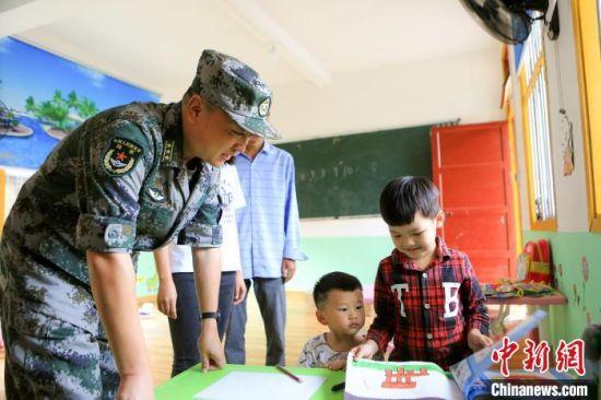 图为查看村小学及幼儿园儿童学习情况。东部战区73集团军 供图