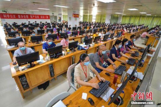 资料图:7月17日,评卷教师们佩戴口罩在位于海南师范大学的海南高考评卷现场工作。 中新社记者 骆云飞 摄