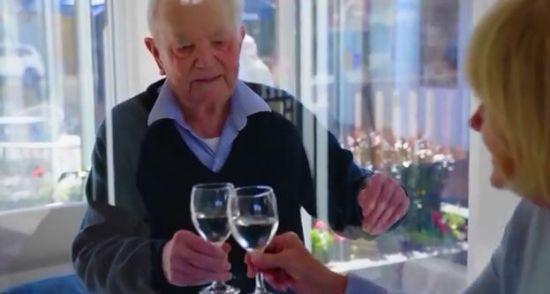 养老院老人同家人隔着玻璃见面、碰杯。图片来源:养老院在社交媒体上发布的视频截图。