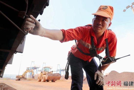 图为调车长朱志翔在罗屿港检查车辆状态,并进行车辆拉风作业,确保车辆以安全的状态连挂成列,安全发车。