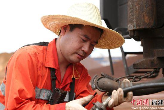 图为调车长马跃飞正在罗屿港安装列尾装置,做列车出发前的准备工作。