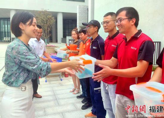 图为主办方为快递(外卖)小哥赠送医护爱心包和文具包。
