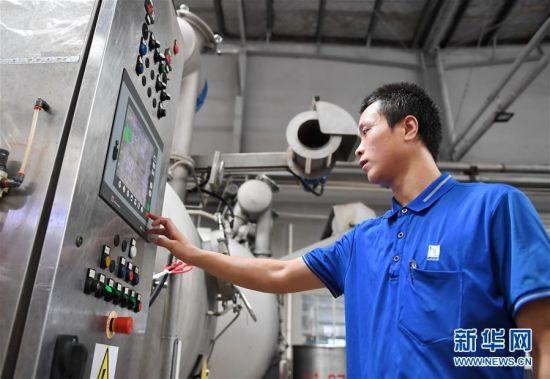 9月8日,来自定西的岳合明在福建东龙针纺有限公司操作染织机器。新华社记者 林善传 摄