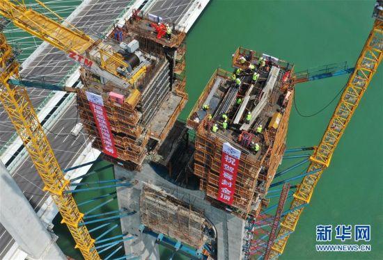 9月15日,施工人员在新建福厦铁路泉州湾跨海大桥塔顶紧张施工(无人机照片)。 当日,新建福(州)厦(门)铁路泉州湾跨海大桥南岸主塔成功封顶。该跨海大桥是新建福厦铁路重点控制性工程,全长约20公里,海上桥梁长约9公里。新建福厦铁路设计时速350公里,预计2022年通车。 新华社记者 林善传 摄
