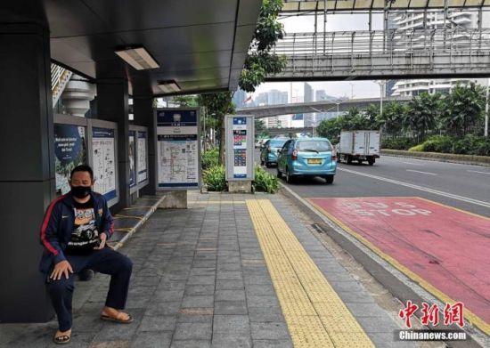 """9月14日起,因疫情持续恶化,印尼首都雅加达第二次实施暂定为期两周的""""大规模社会限制""""措施。图为一市民佩戴口罩在公交停靠站候车。 中新社记者 林永传 摄"""