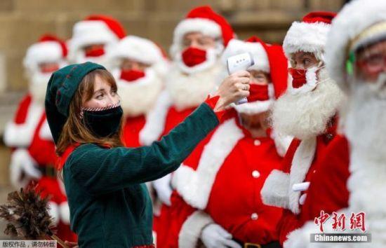 资料图:当地时间8月24日,英国伦敦,培训圣诞老人的课程在南华克大教堂举办,前来参加培训的圣诞老人们需要进行体温检测,上课全程佩戴口罩。