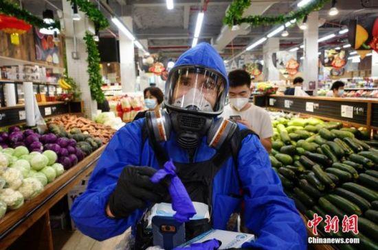 资料图:当地时间9月7日,一位市民身着防护服头戴防护面具在纽约皇后区一家超市为顾客发手套、口罩等抗疫物资。中新社记者 廖攀 摄