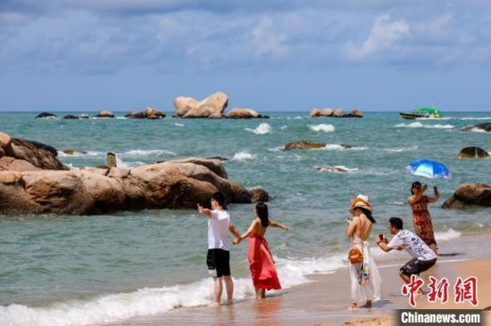 """游客在天涯海角的海边沙滩""""拥抱大海""""。 范勇 摄"""