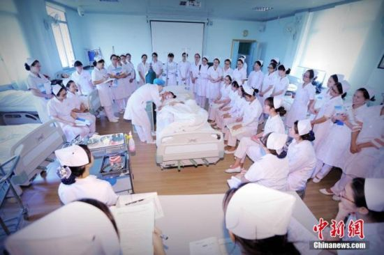 """资料图:桂林医学院一堂普通的护理实习操作课,课程的题目是口腔护理。老师正在用手电筒检查""""患者""""口腔是否有异物。裴蕾 摄"""