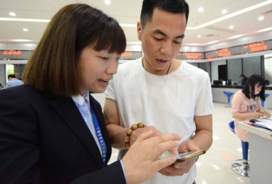 工作人员指导市民使用网上政务服务。