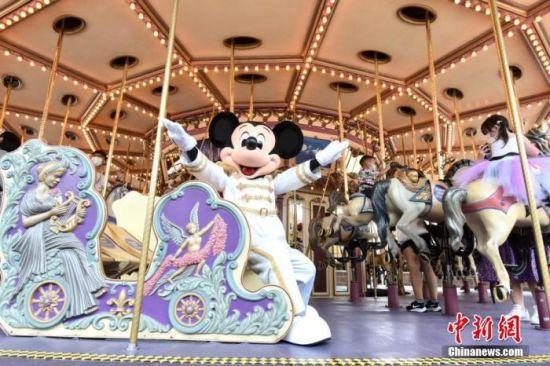 9月25日,市民与香港迪士尼乐园经典角色米老鼠一起乘坐灰姑娘旋转木马。香港新冠肺炎疫情放缓,香港迪士尼乐园重新开放。中新社记者 李志华 摄