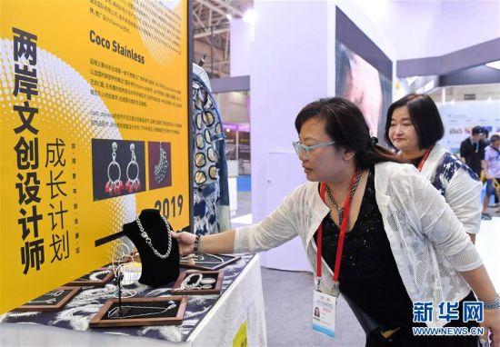 台湾文创设计师林静瑜(前)在第二十一届海峡两岸经贸交易会上介绍她设计的饰品。 新华社记者 林善传 摄