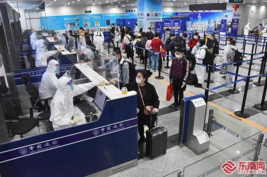 1月31日,入境旅客在福州机场边检站旅检大厅内保持一米间距有序办理通关手续。林辉 宋华龙 摄