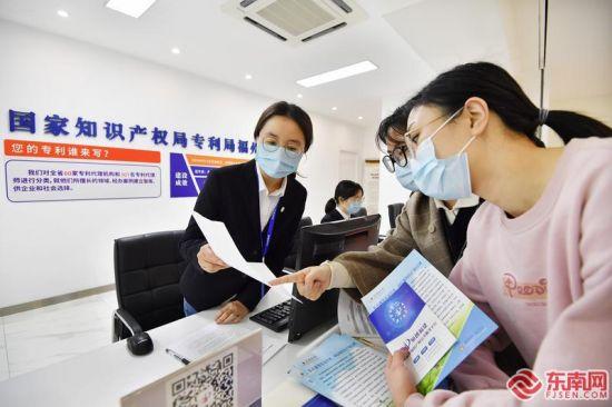 """7日,在""""知创福建""""福建省知识产权公共服务平台服务大厅内,工作人员(左)在为企业代表提供专利申请咨询。本报记者 林辉 摄"""