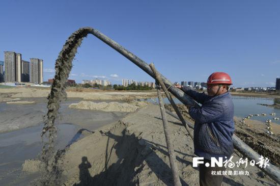 工人坚守一线,对湖底进行抽沙。记者 池远 摄