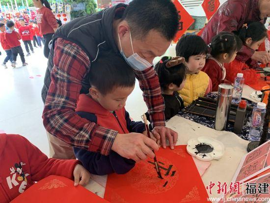 学生家长教小朋友写字。