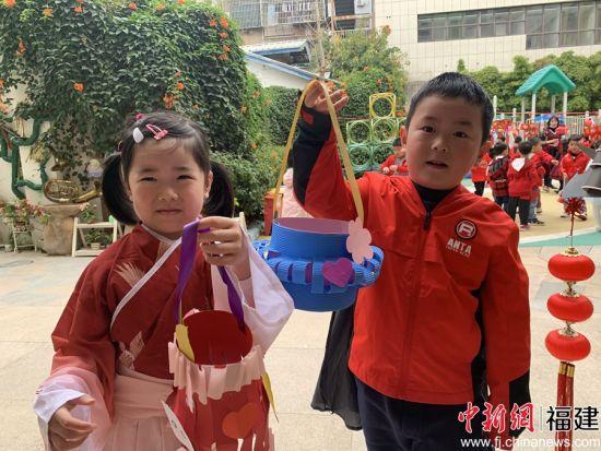 两个小朋友拿着自己亲手制作的花灯合影。