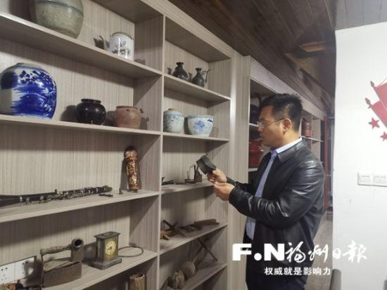 琅岐村村主任李桂锋介绍乡愁小楼里的老物件。记者 余少林 摄