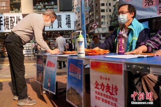 """资料图:香港市民签名支持完善香港选举制度,落实""""爱国者治港""""。 中新社记者 张炜 摄"""